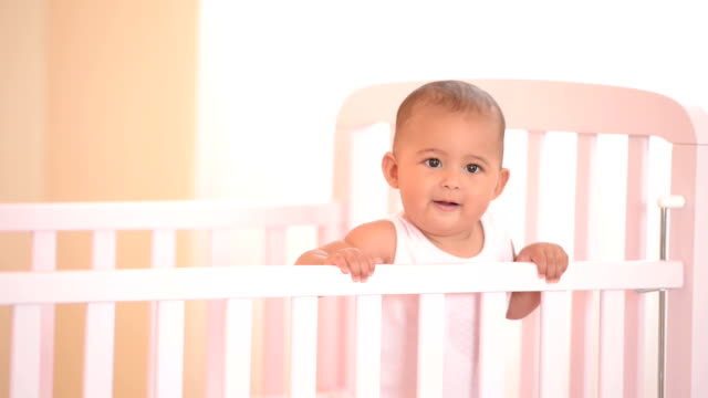 Smiling baby in her crib.