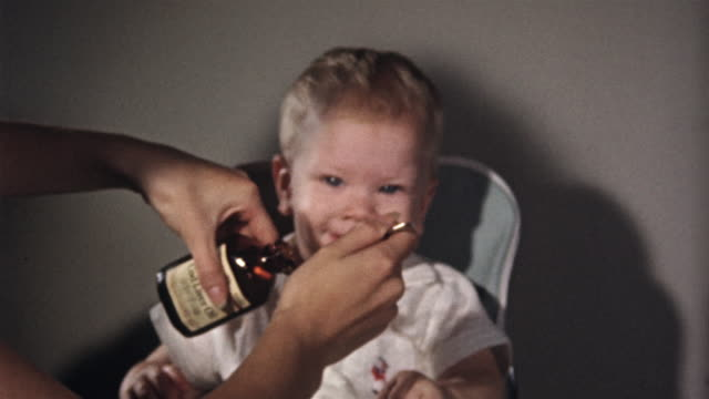1955 MS Smiling baby taking cod liver oil from spoon and coughing/ USA