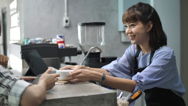 Smiling barista serving a coffee to her customer