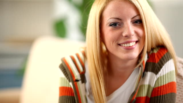 Smiling blond woman sitting on sofa.