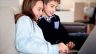 Smiling boy and a girl using lap top at home