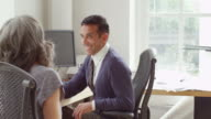 MS Smiling businessman and businesswoman in discussion at office workstation