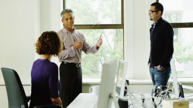 MS Smiling businessman leading discussion with coworkers during informal meeting at office workstation
