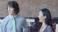 MS Smiling businesswoman and businessman standing in discussion during informal meeting with coworkers in office