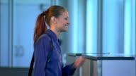 A smiling businesswoman checks her watch as an unseen flight attendant checks her ticket at the gate.