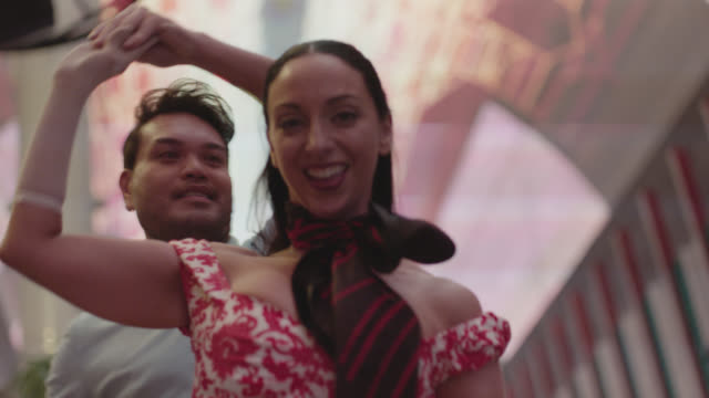 SLO MO. Smiling couple dance in Downtown Las Vegas.