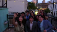 MS HA Smiling family and friends taking selfie with smartphone on restaurant deck