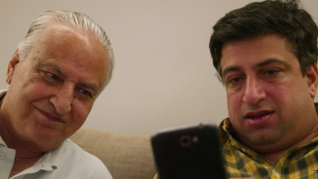 Smiling father and his son sharing a video on a mobile device