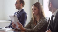MS Smiling female business executive reviewing paperwork during meeting with colleagues in office conference room
