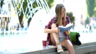 Smiling female reading a book in the park