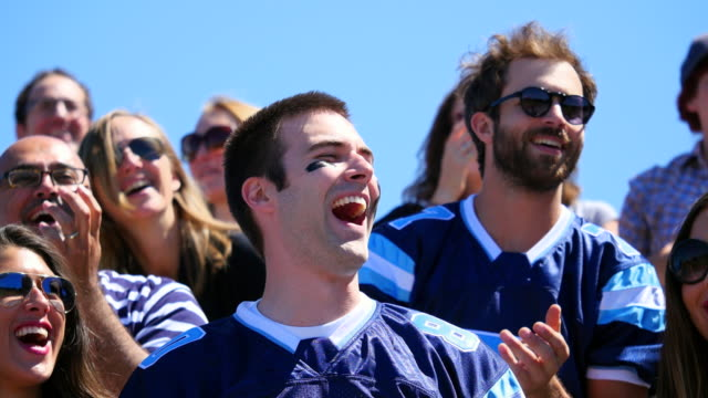 MS Smiling football fan laughing and cheering with friends in stadium during game