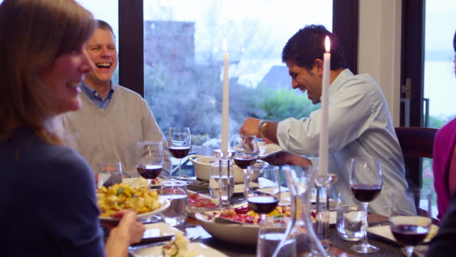 MS Smiling friends passing plates of food at dining table in home