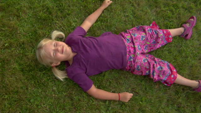 ZO, MS, HA, Smiling girl (4-5) lying on grass, Vinal Haven, Maine, USA