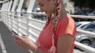 Smiling girl texting on phone while sitting outdoors
