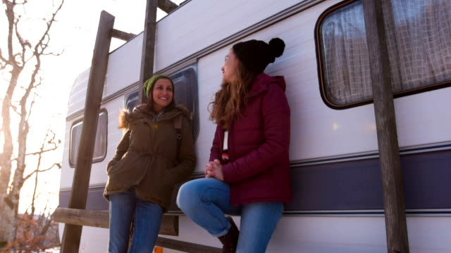 Smiling girlfriends in front of a vintage camper trailer