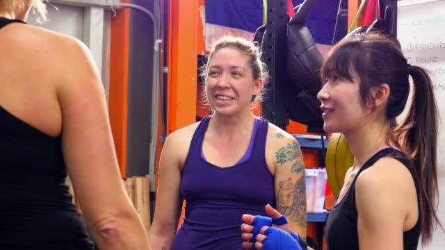 MS Smiling group of female fighters in discussion during training session in gym