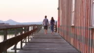 MS Smiling husband and wife couple walking down dock holding hands leaning against railing watching sunset