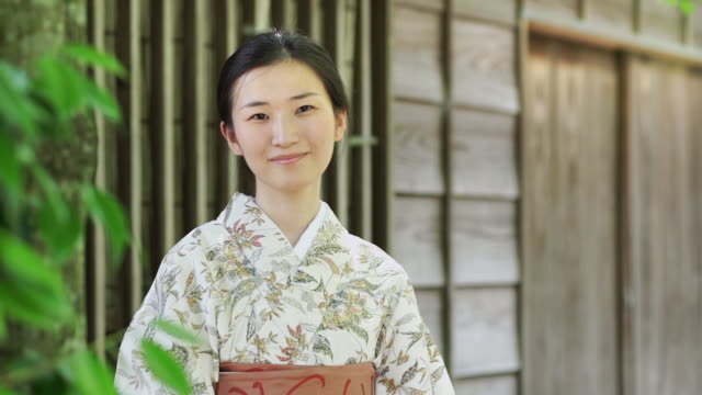 Smiling Kimono Wearing Woman Outside Wooden Building
