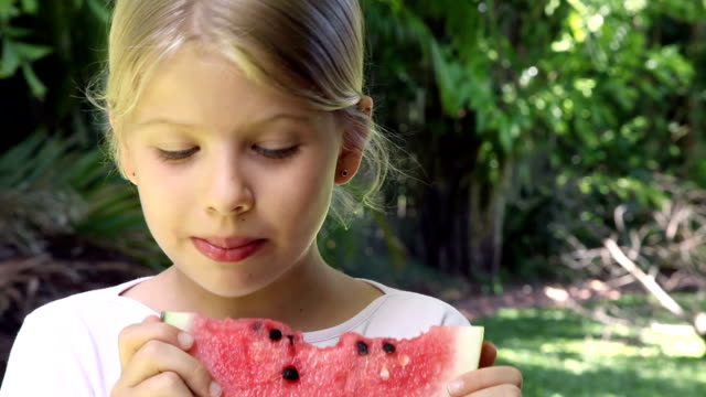 Smiling little girl eating red watermelon fruit outdoors