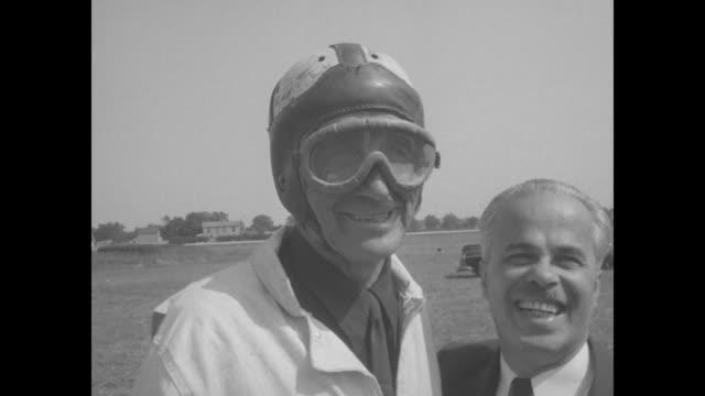 VS smiling man helps stunt man don helmet goggles driver waves / VS same unhelmeted stunt man works with sticks of dynamite box reads 'Du Pont...