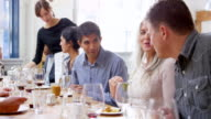MS smiling man in discussion with friends at table in restaurant during dinner party