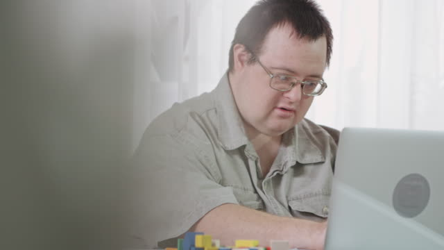 Smiling man with Down syndrome using laptop and working at home