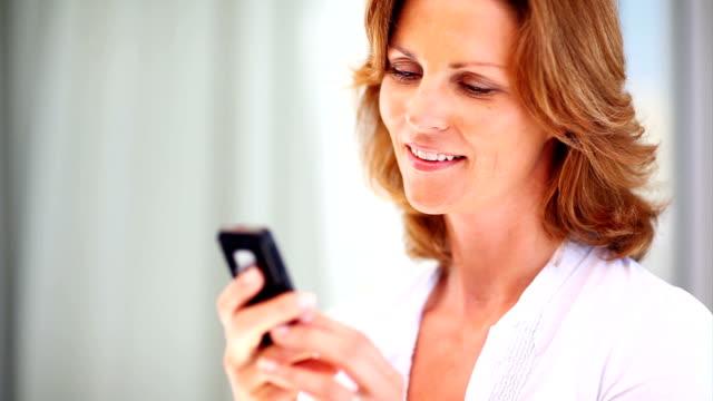Sorridente donna matura leggendo un messaggio di testo