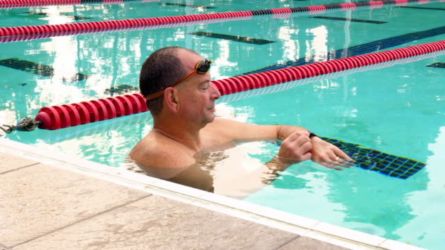 MS Smiling mature male swimmer looking at fitness watch after early morning workout in outdoor pool