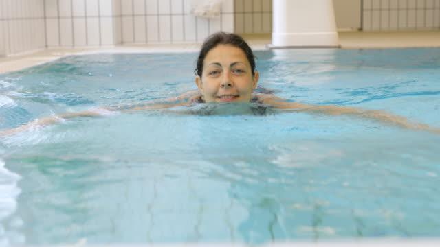 Glimlachend volwassen vrouw zwemmen in zwembad bij aquagym