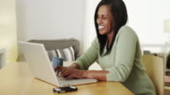 Smiling mature woman using laptop computer at desk