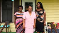 MS ZO Smiling mother and adult daughters standing on front porch of home before church