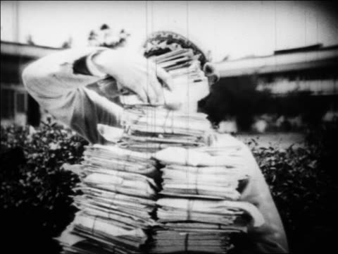 B/W 1925 smiling Norma Shearer holding large stack of fan mail outdoors / she drops it / documentary