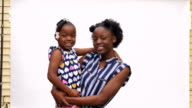MS ZI ZO Smiling older sister standing against white background holding younger sister