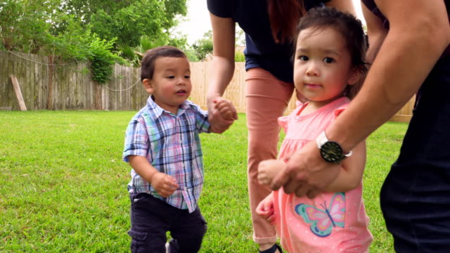 MS Smiling parents introducing toddlers during backyard party