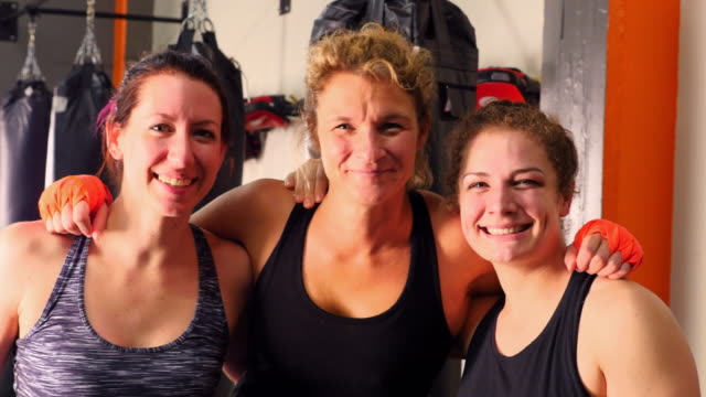 MS Smiling portrait of three female fighters in training gym