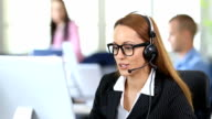 HD Smiling redhead woman with headset and eyeglasses using computer in modern office