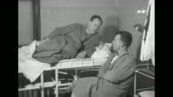 VS smiling woman and men in hospital beds some with bandages / VS group of rescued passenger men sit on hospital bed smoke cigarettes and talk some...