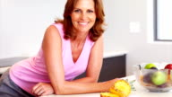 Smiling woman leaning on kitchen counter