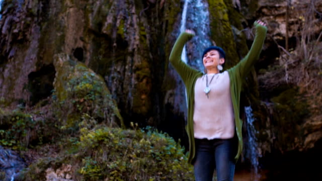Smiling woman outstretching arms in nature
