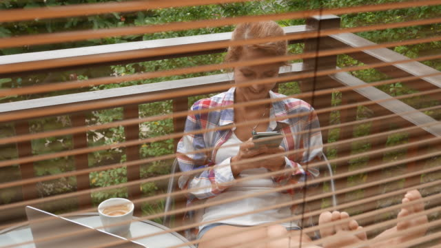 Smiling woman relaxing at the balcony and texting on smartphone