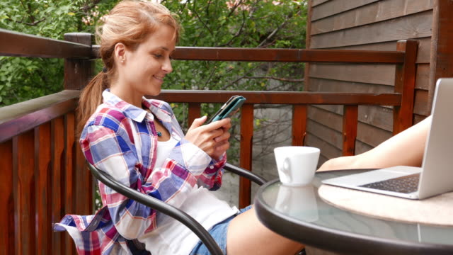 Smiling woman relaxing at the veranda and texting on smartphone
