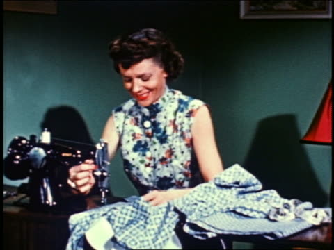 1955 smiling woman sewing fabric with the sewing machine