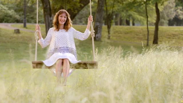 SLO MO DS lachende vrouw swingen in het park