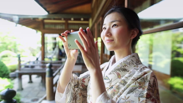 Smiling Woman Taking Photograph at Shrine