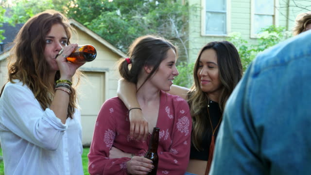 MS Smiling woman with arm around friend hanging out at backyard party on summer evening