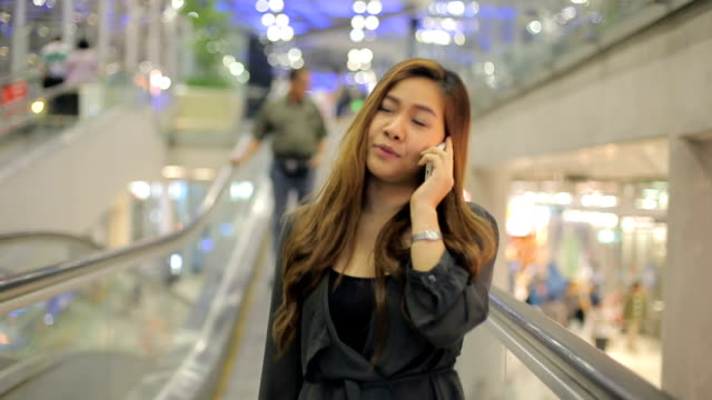 Smiling young asian businesswoman talking on her cell phone