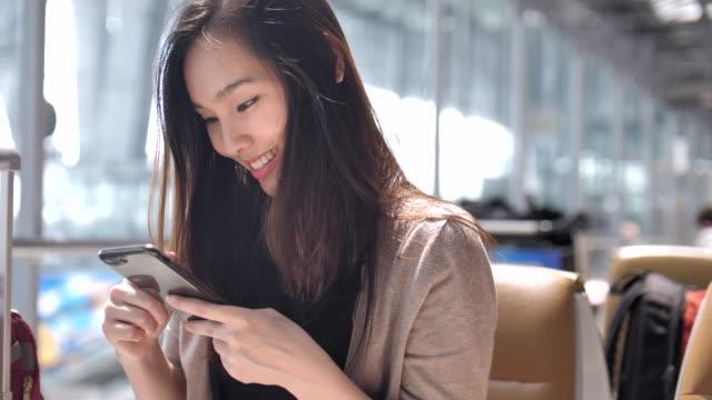 Lächelnde junge Asiatin mit Smartphone am Flughafen
