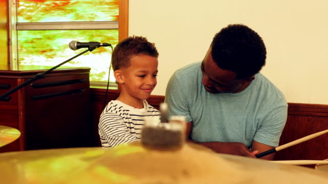 MS Smiling young boy during music lesson on drums with father