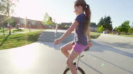 MS TS SLO MO Smiling young girl riding unicycle on cement pathway in playfield near school with friends nearby