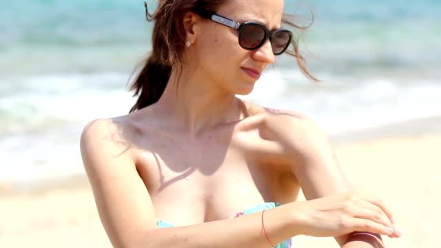 Lächelnde Junge Frau anwenden sun Creme am Strand